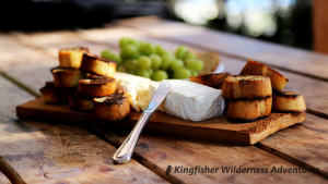 An appetizer of baked brie, baguette, and grapes.